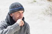 Attractive man smiling on the beach in hat and scarf on a bright but cool day
