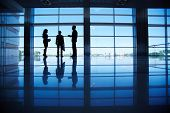 Silhouettes of several office workers standing by the window and talking