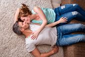 kissing couple couch floor lying down in new home