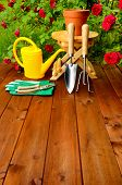 Copyspace gardening tools on wooden table and rose flowers background