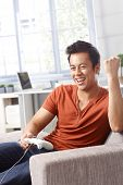 Young man happy for scoring in video game, playing at home, sitting on sofa.