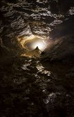 Vertical photo of bright light in a dark cave