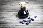 Blueberry Syrup In Glass Bottle Or Mixture, On Wooden Background.