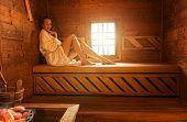 Pretty woman alone, in bathrobe, enjoying the sauna