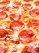 Appetizing background pepperoni pizza closeup filling the frame.