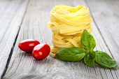 Italian Pasta Fettuccine Nest With  Tomatoes And Fresh Basil Leaves,
