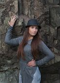 Beautiful young woman in black hat at the rock