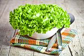 lettuce salad in a bowl and spoons closeup on rustic wooden board