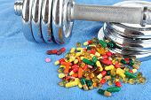 Dumbbell and colorful pills, tablets, on color background