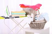 Basket with laundry and ironing board on light home interior background