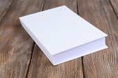 White book on wooden table, close-up