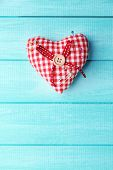 Fabric heart with color and safety pins on wooden background