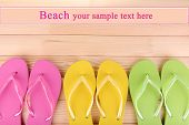 Bright flip-flops on wooden background
