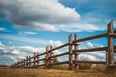 Wooden Rustic Fence In Village And Blue Sky