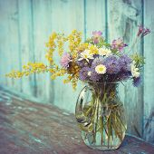 Bouquet Of Garden Flowers And Healing Herbs In Glass Jug On Old Bench