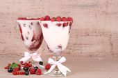 Tasty raspberry dessert with berries on pink wooden background