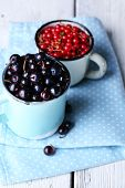 Summer berries in color mugs on color wooden background