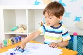 Cute little boy painting in room