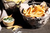 Tasty french fries in metal basket and potato chips on wooden table with dark light