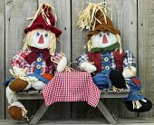 Boy and girl scarecrows sitting at picnic table