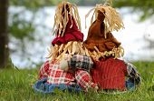 Boy and girl scarecrows back view sitting by lake