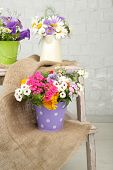 Bouquet of colorful flowers in decorative buckets, on wooden ladder, on home interior background