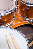 foto of drum-kit  - Two drumsticks on top of a drum kit - JPG