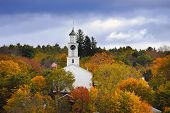 image of church-of-england  - White country church and American flag surrounded by autumn colors in New England