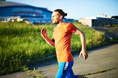 Portrait of young attractive sportsman with earphones running outside
