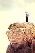 standing man on rock natural cliff