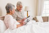 Senior couple relaxing in bed at home in bedroom