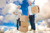 Older couple smiling at camera with moving boxes against blue sky with white clouds