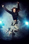 Beautiful hip-hop dancer jumping over grunge background.