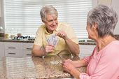 Senior couple playing cards at the counter at home in the kitchen