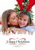 Loving mother kisses daughter at Christmas against border