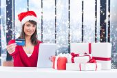 Festive brunette shopping online with tablet pc against glittering lights in room