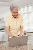 Senior man using his laptop at home in the kitchen