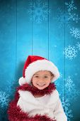 Cute little girl wearing santa hat and tinsel against snowflake pattern on blue planks