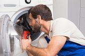 picture of washing-machine  - Handyman fixing a washing machine in the kitchen - JPG