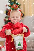 image of rudolph  - Festive little boy smiling at camera with gift against snow falling - JPG