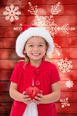 Cute little girl wearing santa hat holding bauble against snowflake pattern on red planks