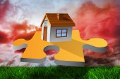 House on jigsaw piece against green grass under red cloudy sky