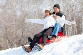 stock photo of sled  - Mature couple sledding - JPG