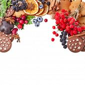 christmas frame of cookie , berries , fruits , different xmas ingredients and spices on a white background