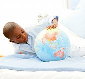 Cute Little Boy Playing With A Terrestrial Globe