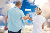Happy older couple painting white wall against blue sky with white clouds