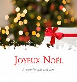 Joyeux noel against focus on christmas gift and pine cone
