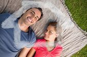 Two friends looking towards the sky while lying on a quilt against house outline in clouds
