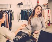 foto of showrooms  - Happy woman customer paying with credit card in fashion showroom - JPG