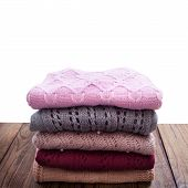 Knitted Clothes On Wooden Background.